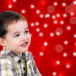 Cute little boy on red background with lights — Stock Photo
