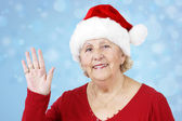 Christmas hat grandma waving over blue — Stock Photo