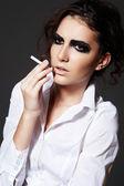 Beautiful woman model smoking a cigarette. Dark rock make-up — Stock Photo