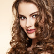 Lovely model with shiny volume curly hair. Pin-up style on beige background — Stok fotoğraf