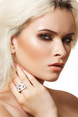 Beautiful blond woman model with brown smoky-eye make-up and white ring — Stock Photo
