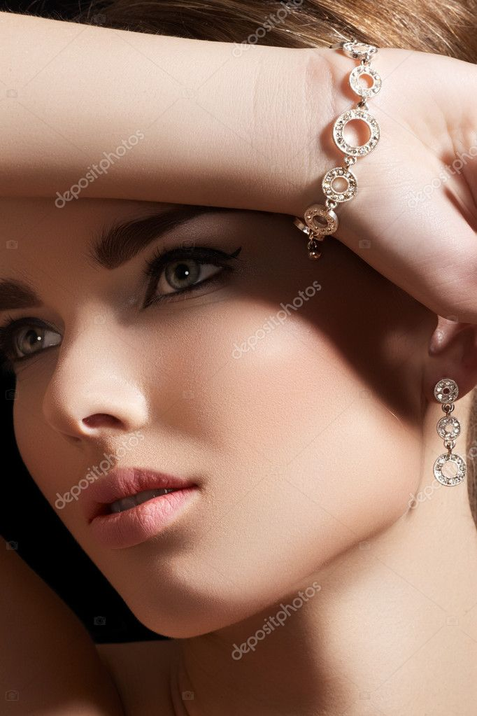 Beautiful woman model in retro style make-up. Accessories, jewelry gold bracelet.  Stock Photo #7839811
