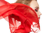 Fashionable portrait of a girl model with waving red silk scarf — Stockfoto