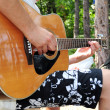 Young man playing acoustic guitar in the nature - Stockfoto