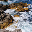 Waves splashing into rocks - Stock Photo