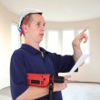 Young serious man with drill and paper hat in new building — Stock Photo
