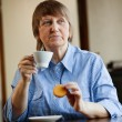 Senior woman having coffee with cookie — Stock Photo