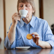 Stock Photo: Woman having coffee and cookie