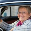 Senior woman in oldtimer car — Stock Photo