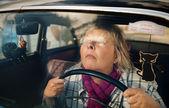 Senior woman in oldtimer car — Stock Photo
