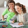 Girl doing homework with her mom — Stock Photo #7231304