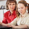 Girl and her mother with laptop at home — Stock Photo