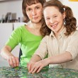 Teenager girl assembling jigsaw with her mother — Stock Photo