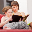Mother and daughter reading book together — Stock Photo