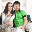 Smiling couple watches TV — Stock Photo