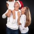 Family on a black background, Santa's hat with dad. — Stock Photo