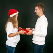 The man gives the gift pregnant girl in Santa hat — Stock Photo
