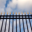 Steel fence with gold spears — Stock Photo