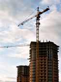 Stand, house, construction crane in the sky with clouds — Stock Photo