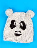 Knitted wool hat with a pattern of little faces — Stock Photo