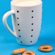 Cupful of milk and bread rings — Stock Photo #7410663