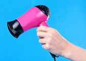 Pink hair dryer in the female hand — Stock Photo