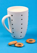 Cupful of milk and bread rings — Stock Photo