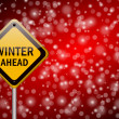 图库照片: Winter ahead traffic sign on snowing background