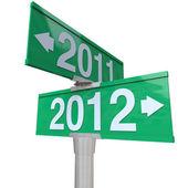 Año nuevo 2012 flechas apuntando desde 2011 en señales de tráfico bidireccionales — Foto de Stock