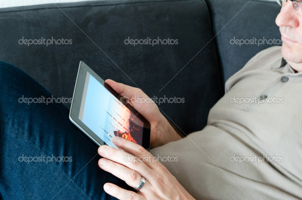 Middle-aged man sitting comfortably on a sofa and checking a digital tablet pc — Stock Photo #6861786
