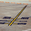 Stock Photo: Airplane parking markings on airport tarmac yellow blue