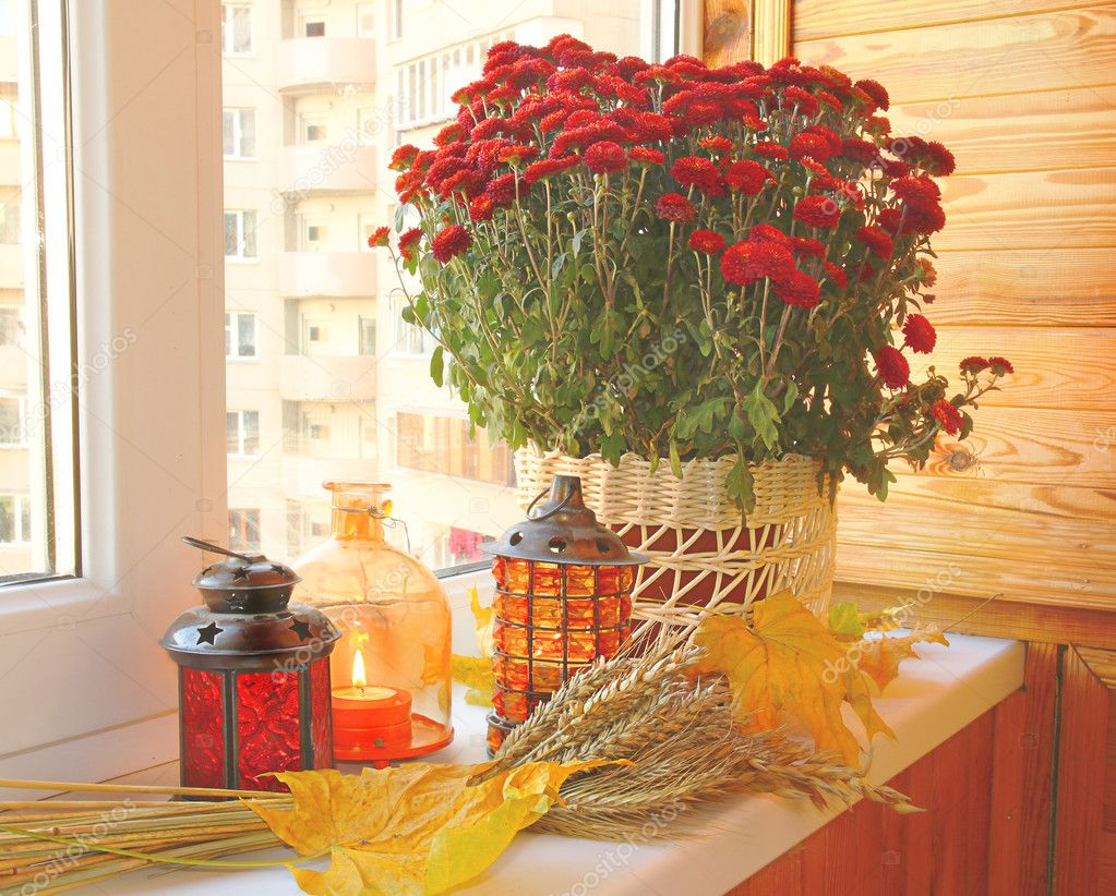 Creation of autumn mood on a balcony by candlesticks, bunch of wheat, yellow leaves and bush of chrysanthemums — Stock Photo #7424268