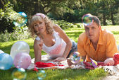 Young couple having a picnic and making bubbles — Stock Photo