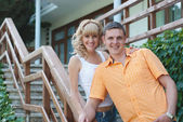 Young couple standing on their front porch — Stock Photo