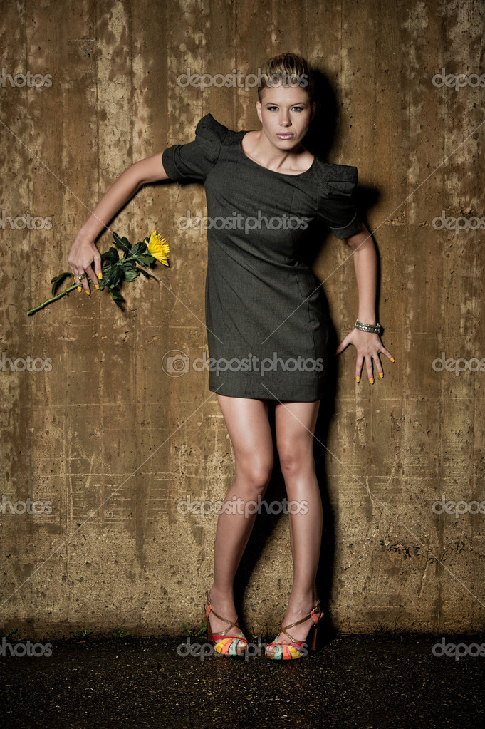 Fashion model posing in an urban setting with a flower — Stock Photo #6803547