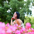 Beautiful girl in park with pink flowers — Stock Photo