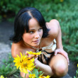 Sexy model in park with flowers — Stock Photo