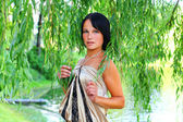 Young serious model in weeping willow — Stock Photo