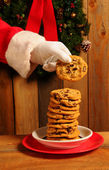 Santa taking cookie from stack on plate — Stock Photo