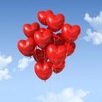赤いハートの形の風船が空に浮かんでいます。 — ストック写真