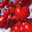 Red heart shaped balloons floating in the sky — Stock fotografie