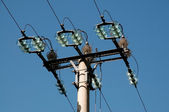 Electrical pole with insulator on blue sky — Stock Photo