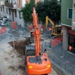 Digger on a city street — Stock Photo