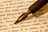 Nib (pen) over an old book — Stock Photo