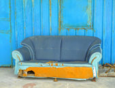 Old abandoned house front with blue sofa — Stock Photo