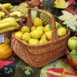 Stock Photo: Autumnal harvest fruit in basket over carpet and leaves