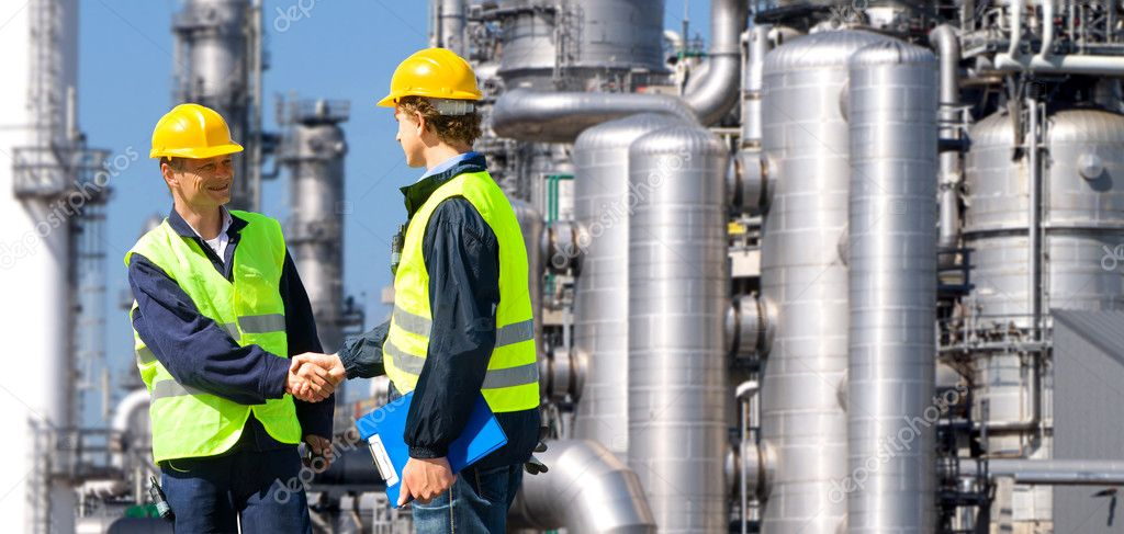 Two petrochemical contractors closing a deal in front of an oil refinary — Stock Photo #7057356