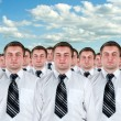 Many identical businessmen clones - Foto Stock