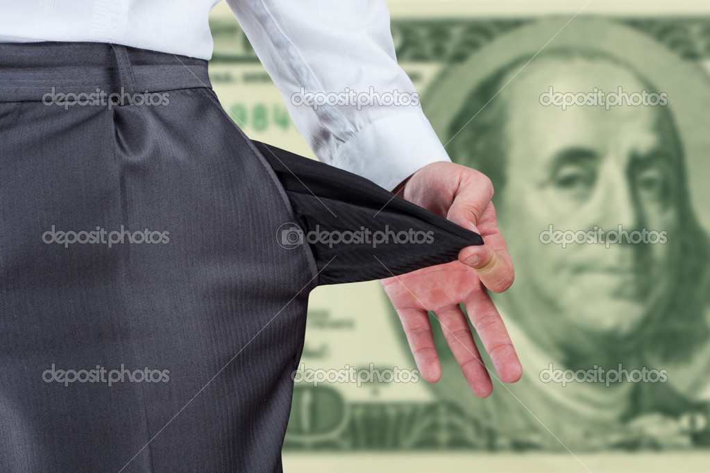 Businessman pulling empty pocket out of pants against dollar banknote — Stock Photo #6840833