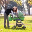 Stock Photo: Young mother carrying baby in autumn park